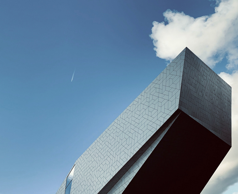 A modern building bisects a clouded sky with oblique angles.